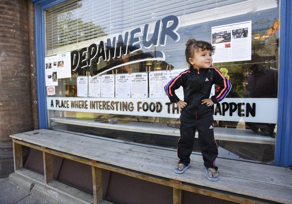 Four-year-old Jore Almasri poses outside the Depanneur, where her mom is inside taking cooking with other Syrian women. (Fred Lum/The Globe and Mail)