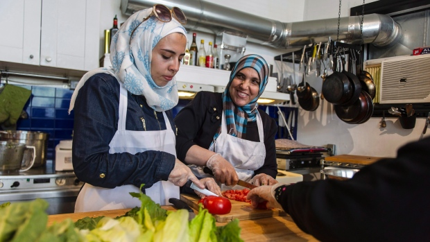 Syrian women prepare food at the Newcomer Kitchen Project, hosted by Len Senater and Cara Benjamin-Pace at the Depanneur restaurant inToronto on July 7, 2016. (Christopher Katsarov/The Canadian Press)